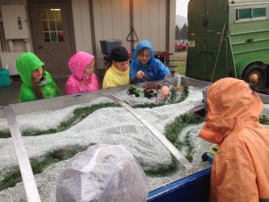 Elementary students gather around the Rolling Rivers Trailer to strategize about how to provide stock water while also protecting riparian areas.